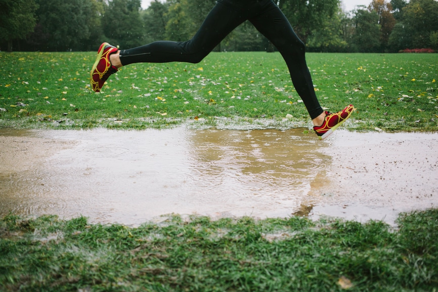 Photo of legs of a runner in the rain jumping over a puddle
